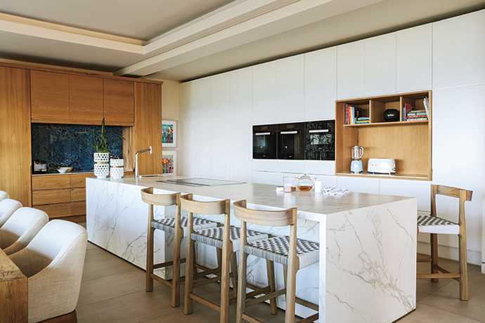 The kitchen's clean lines reflect the strong linearity of the home's architecture. The island is clad in Neolith's Calacatta, and the bold backsplash is a Blue Agata granite slab from Womag.