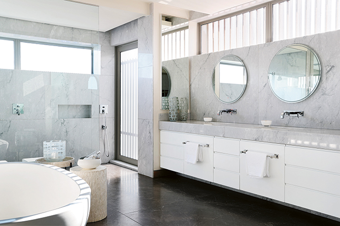 Bianco Carrara marble introduces femininity to an otherwise architectural and masculine master bathroom. The door leads from the his-and-hers showers to a private screened terrace.