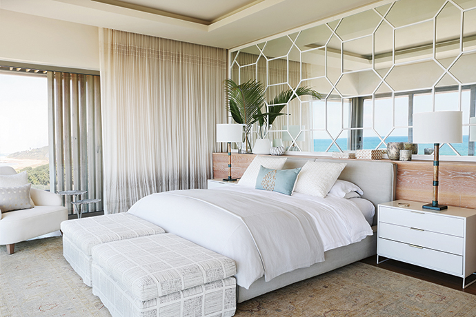 The octagonal Chinese lattice mirror creates a feature wall in the master bedroom. Not only does it reflect endless ocean views, but the graphic pattern also pairs well with Jeffrey Alan Mark's Templin fabric on the ottomans.