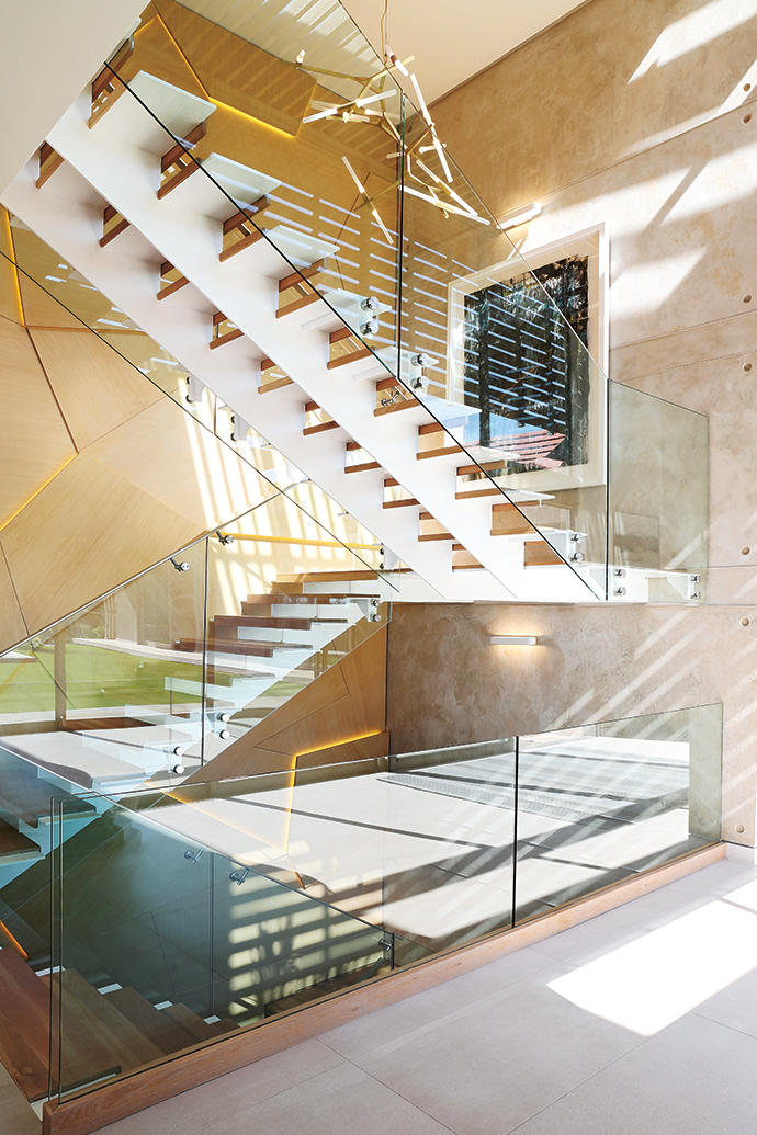 One of designer Kelsey Boyce's favourite spaces within the home, the entrance hall is given rock-star edge by a feature wall comprising backlit geometric timber panels. A slatted ceiling allows for the play of sunlight.