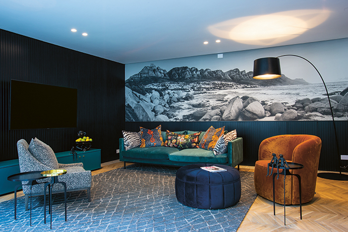 The reading room-cum-TV lounge off the atrium features cosy dark panelling, plush fabrics and a wallcovering of an iconic Cape Town vista.
