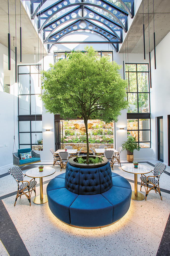 The existing external courtyard was enclosed with steel and glass to create a light-filled double-volume atrium and central dining area. The custom planter and circular sofa was designed by Make Studio and made by Human Kabinette and Daniel Interiors.