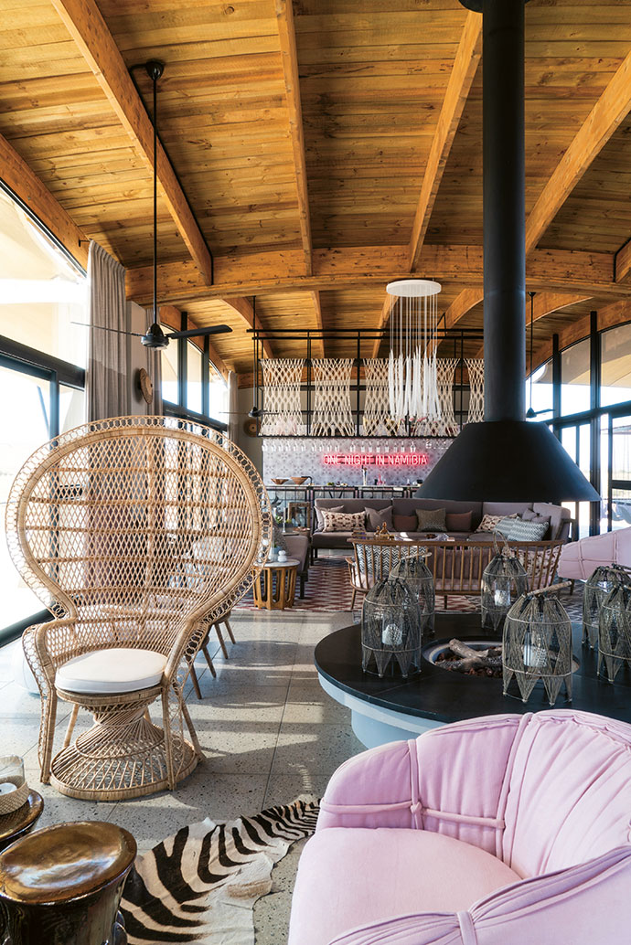 Communal seating areas afford uninterrupted views of the dunes while clashing textures add spirit. The panels above the bar area were custom-designed by Sandy Tsou, and the Scandi-style sofas were created by Houtlander. A central indoor firepit adds warmth on chilly desert evenings.