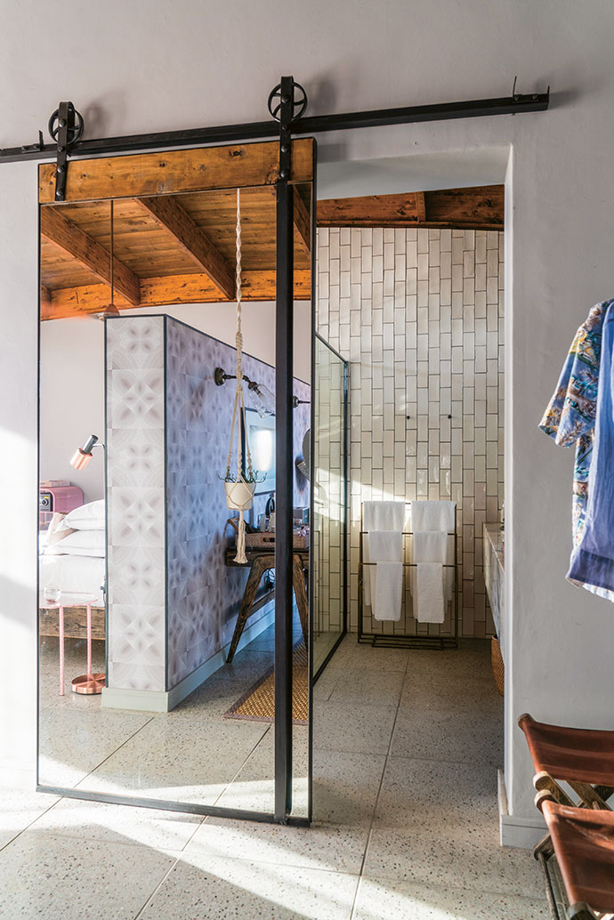 Mirrored barn-style doors offer privacy in the en-suite bathrooms, where Robin Sprong wallpaper, reminiscent of old spirographs, covers the bedroom partition.