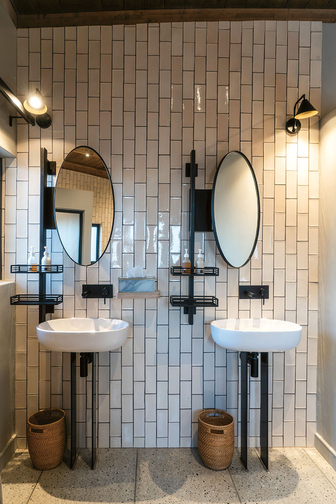 The bathroom tiles from Southern Art Ceramics make a powerful statement against custom basin stands and mirrors.