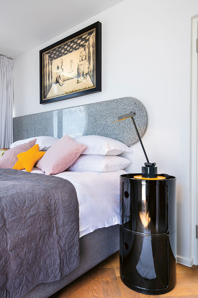 In the main bedroom, a wall-mounted custom granite headboard by Sangengalo Marble & Granite is set above a king-size bed from Cloud Nine (cloudnine.co.za). The artwork is by Karin Jaroszynska and the 1983 Aero Desklamp was designed by Ettore Sottsass for Bieffeplast.