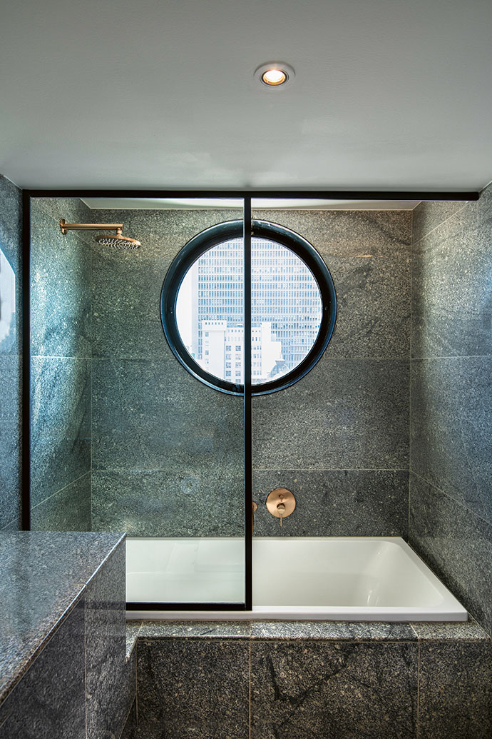 A porthole allows light into the main bathroom. The solid-granite tiling is from Mazista (mazista.co.za), the Villeroy & Boch bath and champagne Meir showerhead and faucets are from Flush Bathrooms (flushbathrooms.co.za). The shower screen is by Showerline (showerline.co.za)