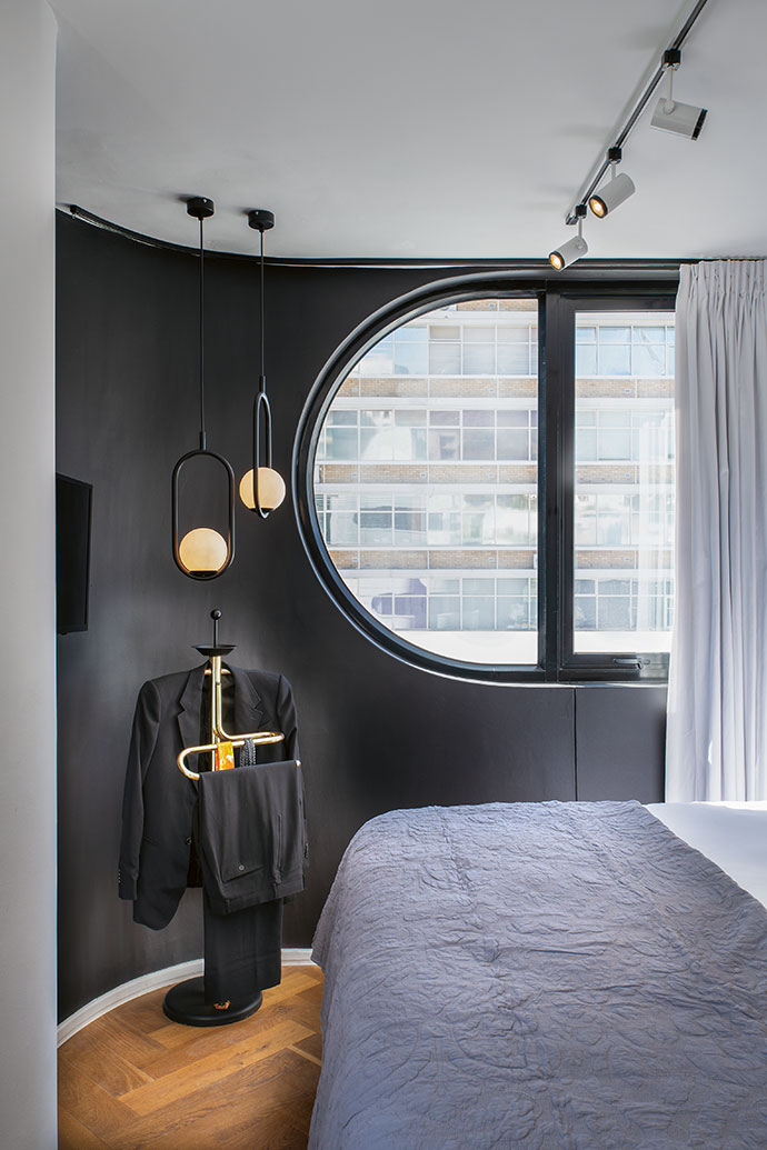 Distinctive capsule-shaped windows frame the view from the main bedroom. The brass dumb valet is from Ride A White Swan, hanging lights from Maxim (maximdecor.net), spotlights from Eagle Lighting (eaglelighting.co.za) and bedding from Woolworths' David Jones collection.