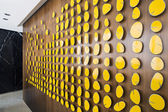 A Carolina Sardi art installation consisting of suspended yellow discs create striking focal points on the wall of the bar.