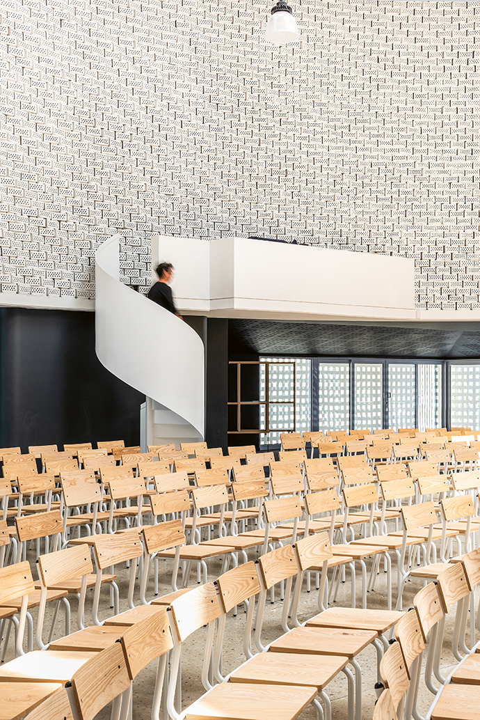 Wood and white steel-framed chairs and a polished concrete floor reflect the pared-down ethos of the building.