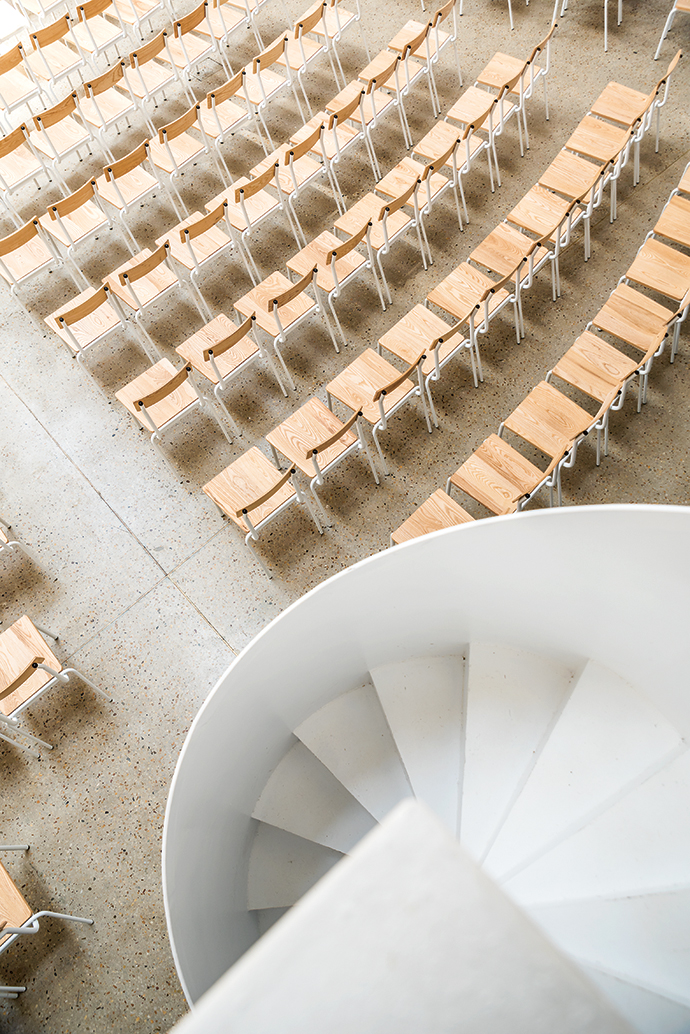 A white steel spiral staircase leads to the sound control desk; brick interior walls create magnificent acoustics in the circular structure.