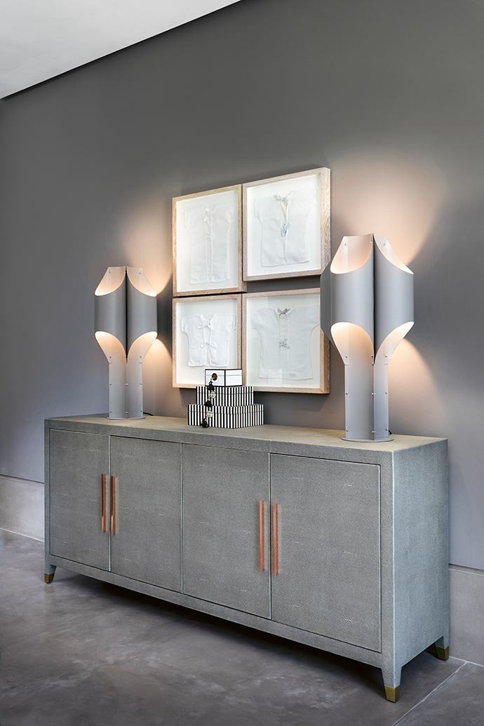 Table lamps from Restoration Hardware in the US sit atop a Graydon Shagreen Collection bureau (also from Restoration Hardware in the US), flanking framed birthgowns of the owner's four children.