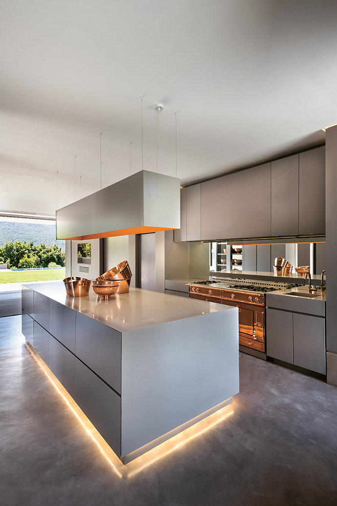Copper-plated fixtures and accents are found throughout the home, including in the open-plan kitchen.