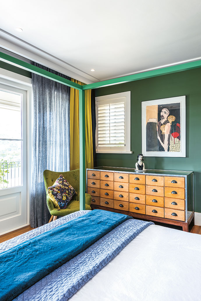 The guest bedroom's antique haberdashery cabinet competes for attention with an artwork by Stephen Allwright.