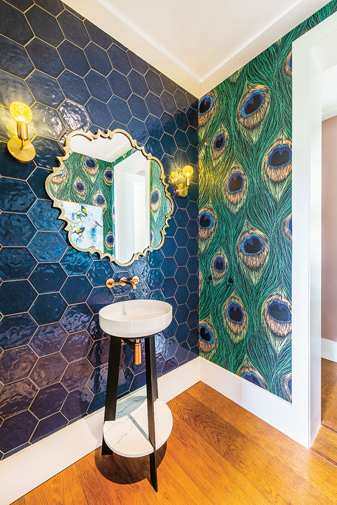 The guest bathroom is appointed in wallpaper by Cara Saven and tiles from Lime Green Sourcing Solutions.
