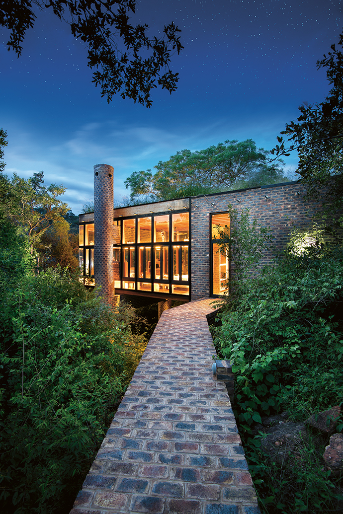 A cliff path through the forest leads to House of the Tall Chimneys. With a perceptible lack of curtains or blinds, the intention is to maximise the building's connection to nature.