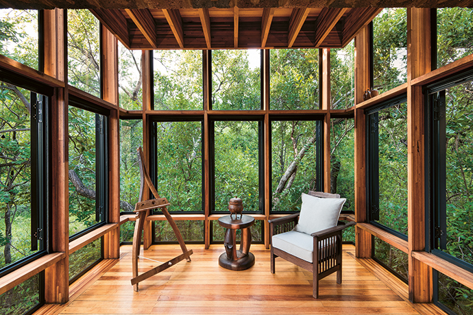 Large windows envelop the bedroom in House of the Tall Chimneys, rendering the divide between indoors and outside imperceptible.