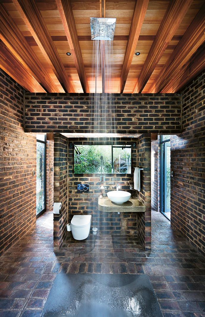 The main bathroom looks out into a courtyard garden planted on the sandstone cliff.