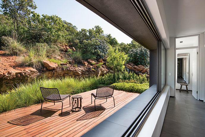 Floating lightly over the indigenous vegetation, all bedrooms have private timber decks stepping into the rocky mountainside. The Lara occasional deck chairs are from Weylandts (weylandts.co.za).