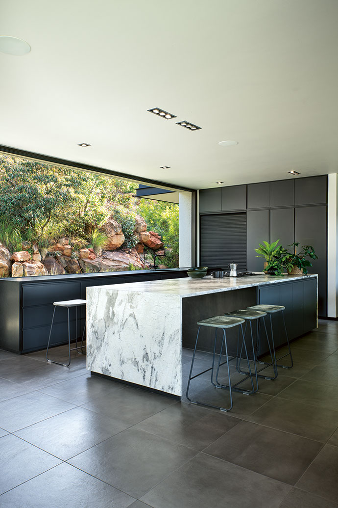 The detailing and finishes were kept clean-cut and minimalist, with nature captured as a piece of art through the window frame. In the kitchen, the sharp geometry of the natural limestone counter marks a vivid contrast to the rich ochre tones of the rocky mountainside.