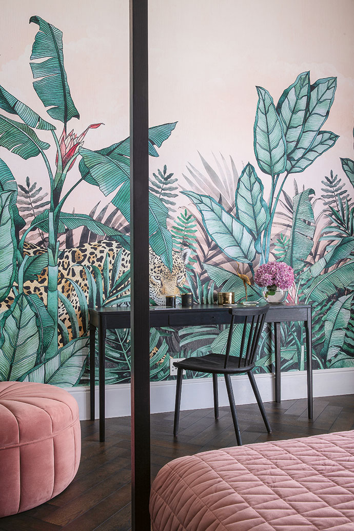 An exotic themed wallpaper by Robin Sprong animates a wall in one of the guest bedrooms.