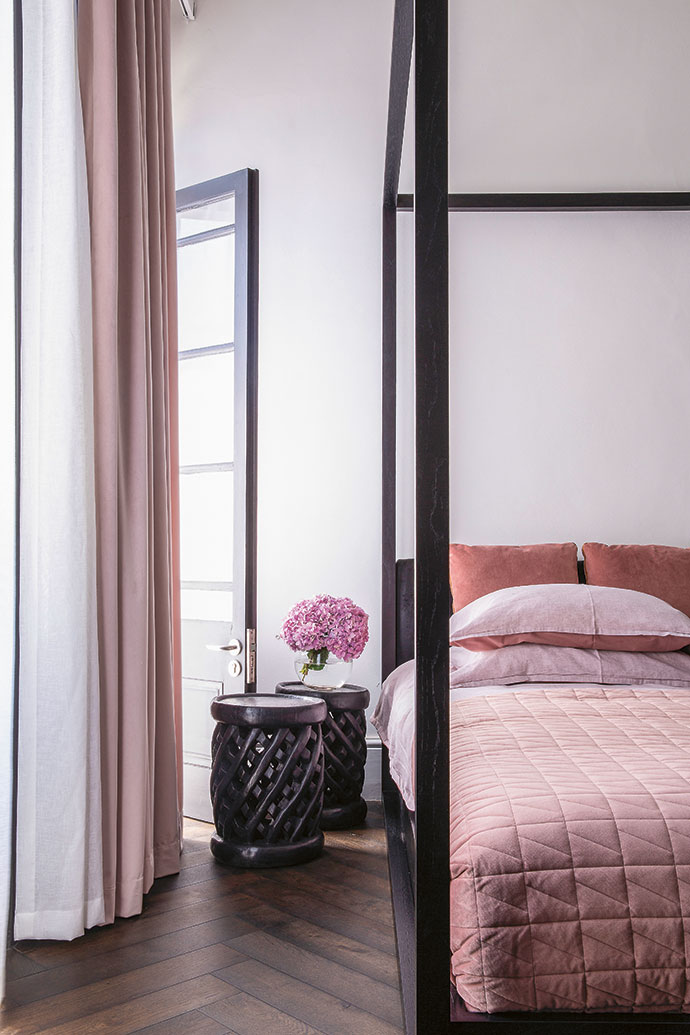 The proportions of one of the guest bedrooms are amplified by a custom-made canopy bed.