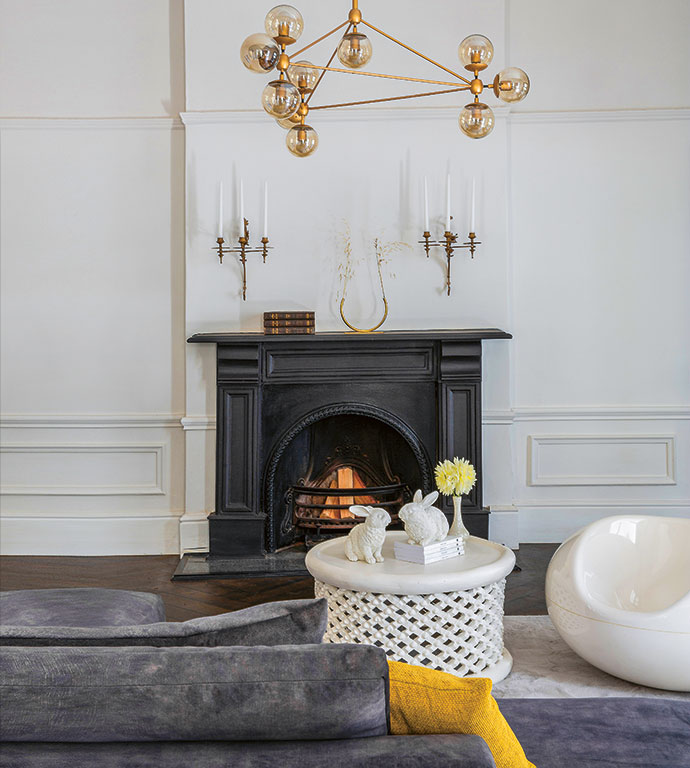 A Modo chandelier from Roll & Hill establishes a contemporary juxtaposition with heirloom candle wall sconces that were originally fixtures of an antique Rococo chandelier.