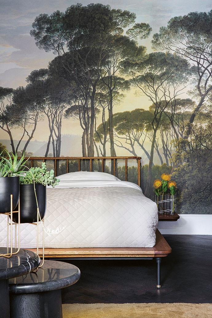 Wallpaper inspired by an Old Masters landscape forms a backdrop for a Distrikt bed by La Grange Interiors.