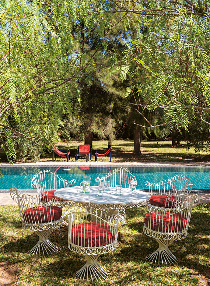 A Mathieu Mathégot table and chairs from Bab El Khemis provide respite near the pool, with vintage armchairs from a St Ouen market in the background.