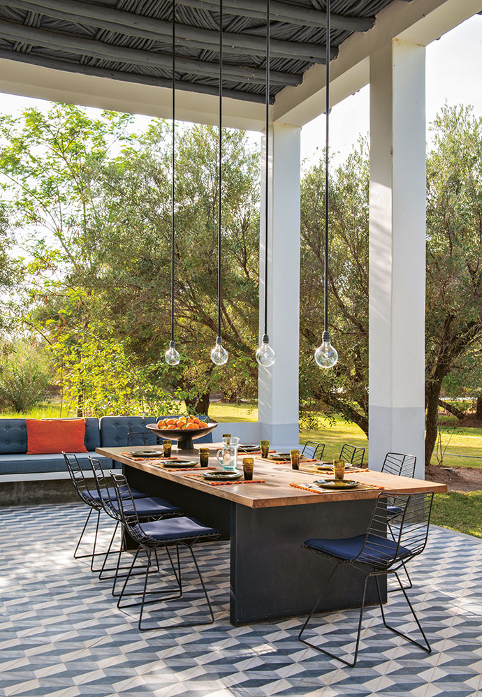 The cement-tiled outdoor dining room features a custom wooden table with steel feet.