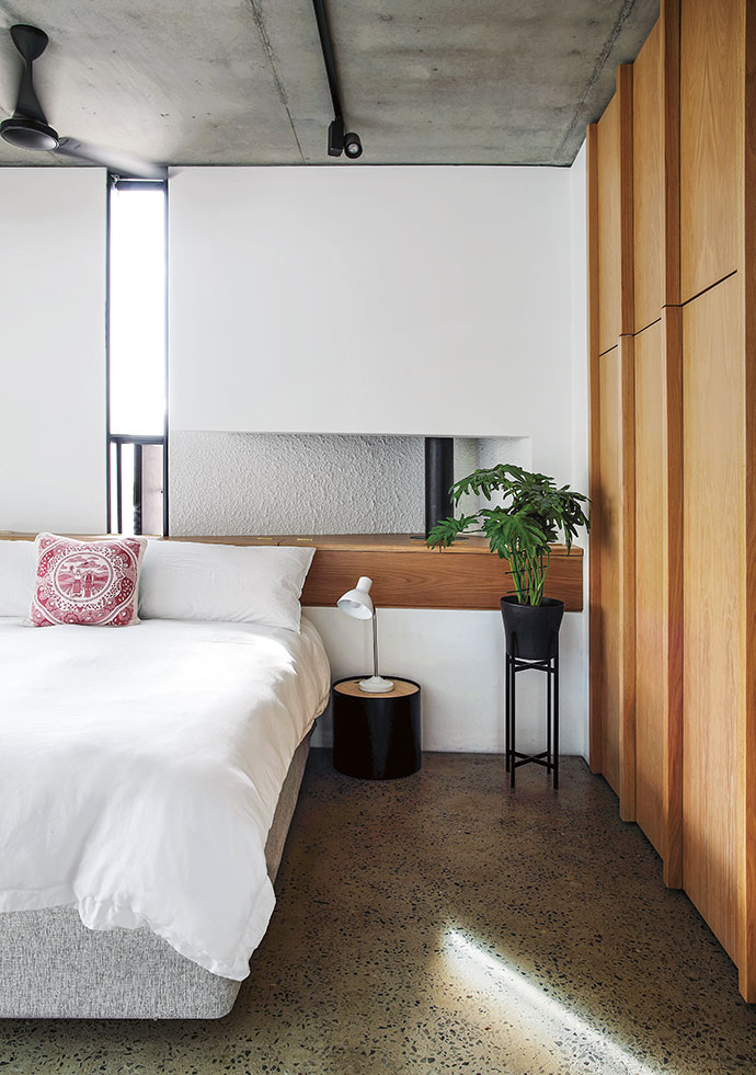 In the main bedroom, light from the skinny window plays on the stipple walls, oak cabinets and polished-concrete floors. The exposed flue allows for radiant heating from the fireplace in the living area below.