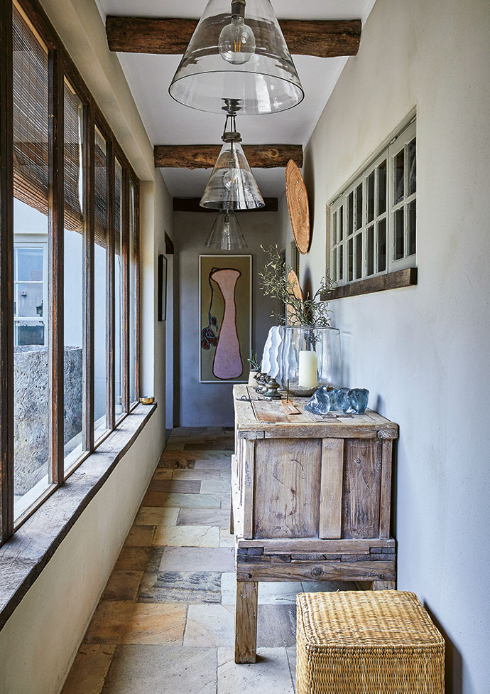 The entrance hall, which connects the kitchen, dining and outdoor areas with the bedrooms and lounge, is dominated by an antique Indian country chest and a Leanne Boulter painting on the far wall.