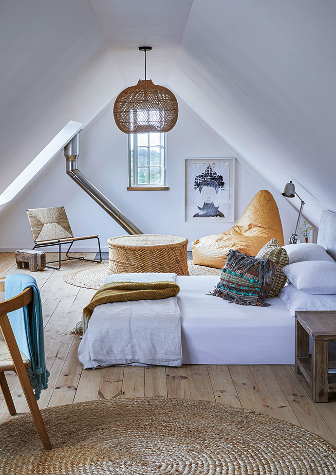 The raw pine floors in Boyd's light-filled loft bedroom are complemented by woven Madwa mats and a light fixture from Eight Degrees South. The beanbag chair is from Cielo, and the wicker chair is from Weylandts. The Anglepoise lamps are from Cécile & Boyd.
