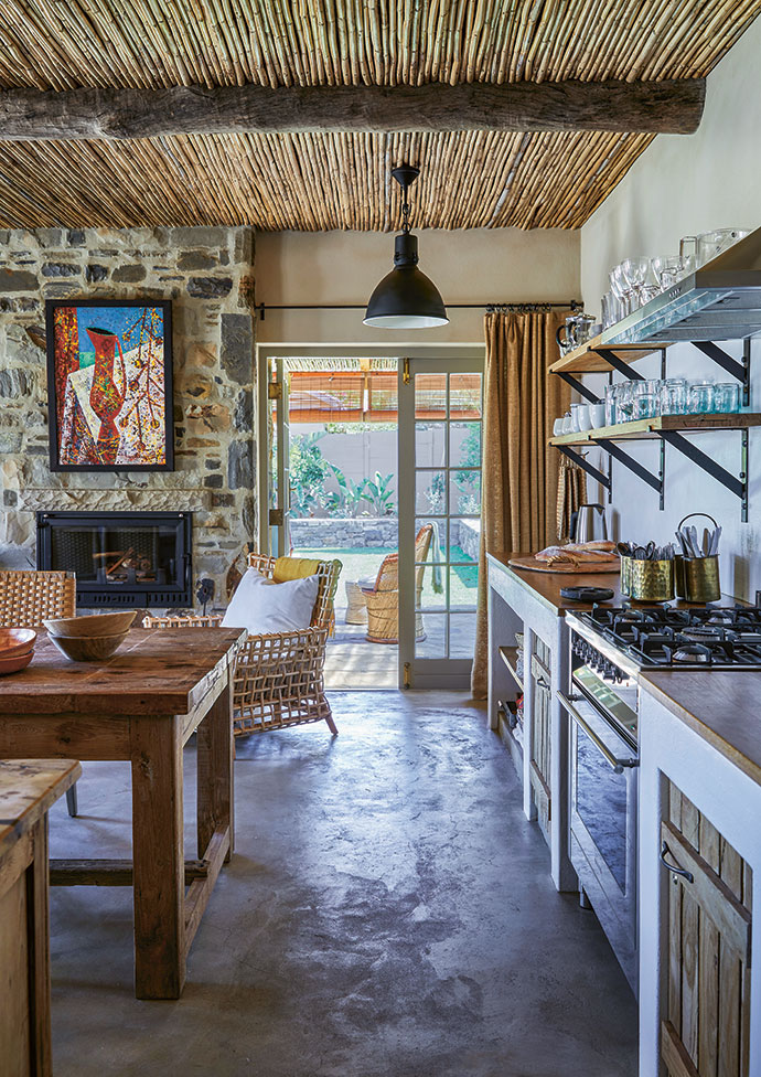 """The kitchen is very much the heart of the home. """"We wanted a simple, utilitarian space where everything could be found at a glance,"""" says Boyd. All counters are built in, with sandblasted wooden shelves and customised steel brackets; the floors are screeded concrete."""