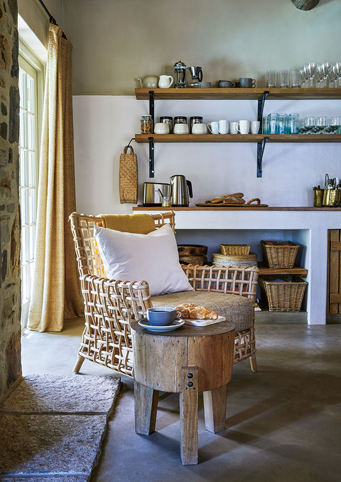 A cane chair next to the fireplace is a cosy corner in which to sit.