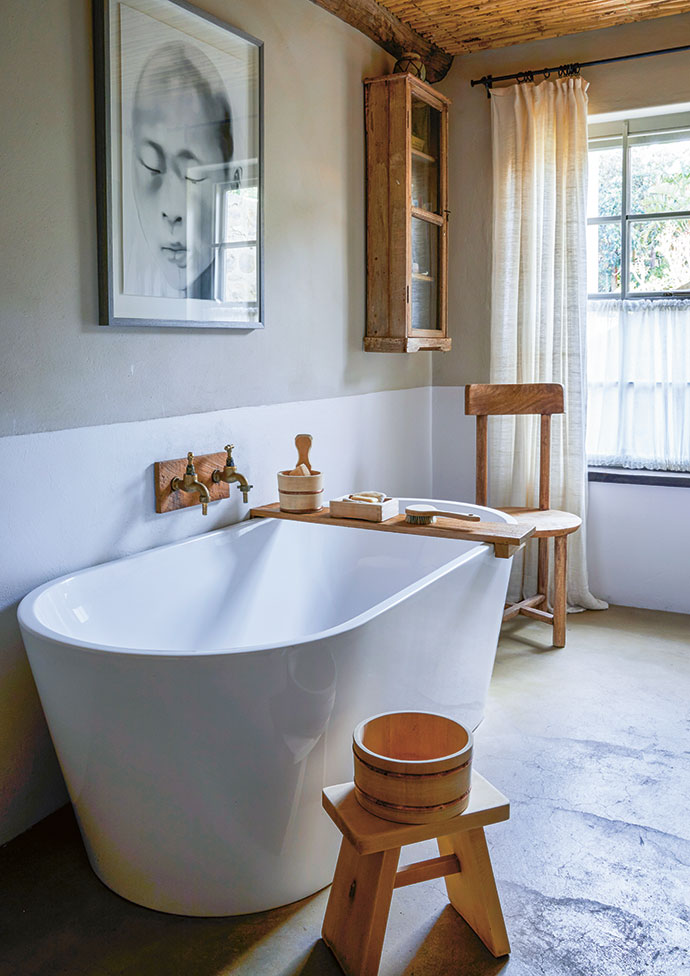 Wooden accents in the bathroom include a Japanese hand basin, and a cupboard and chairs that Boyd sourced in India. The painting above the bath is by Tracy Payne.