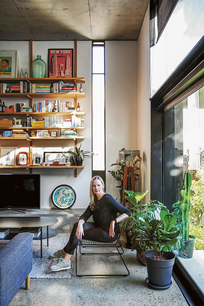 Owner Robyn Campbell in the spacious living area, where custom-made windows create a feeling of height. The floors are a standard Grano screed that has been polished down to reveal the aggregate.