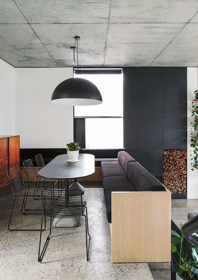 In the elevated dining area, a banquette designed by ML-A and built by Holz Cabinetry creates space-saving seating. The Hee dining chairs by HAY are from Créma, the vintage sideboard is from Space for Life, and the Perspex dome pendant light is from Arc Lighting. The Rocal fireplace, which marks out the living room, was supplied by MacD.