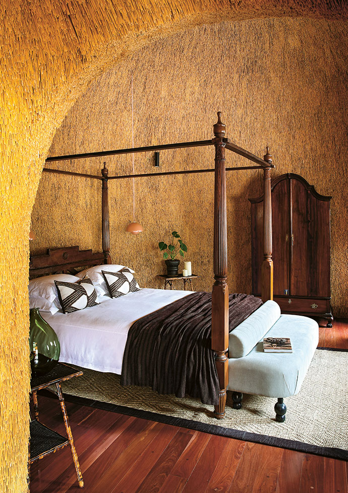The guest bedroom features one of the only beds that could be brought in – an antique four-poster. The room also features an ottoman by Bofred and mid-century finds such as the side tables, the leather chair and the server.