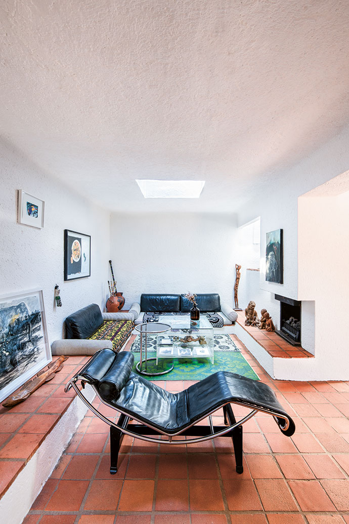The warm quarry tile floors that run throughout the house, white walls and masterful use of natural light seen here in the main living room are classic Sutton features. Featured in the space is Le Corbusier's LC4 chaise longue and Eileen Gray's famous adjustable side table.