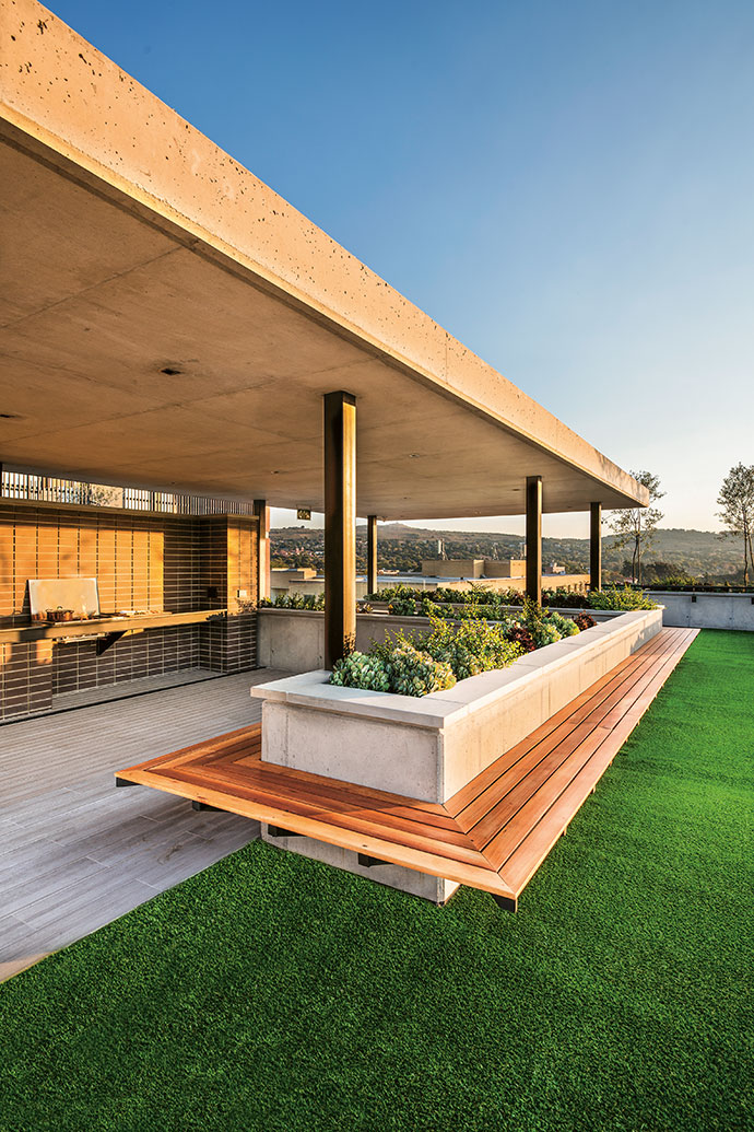 The terrace on the north of the building features a communal braai area with a container garden of indigenous and water-wise landscaping by Earth Art.