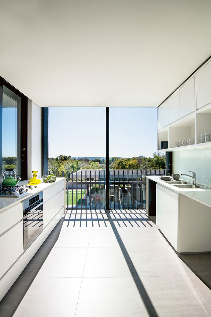 The penthouse kitchen with its leafy outlook, Miele appliances and porcelain tiles, custom-made by NWT. The simple repetition of the mild steel balustrade creates beautiful shadows.