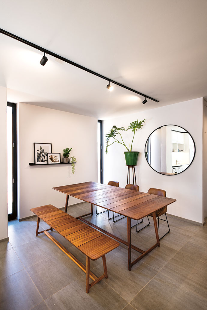 The dining room in one of the three-bedroom units features a table, bench and mirror from Incanda. Floor to ceiling narrow windows not only make the most of the light into the flat but also work to divide the different brick types on the exterior.