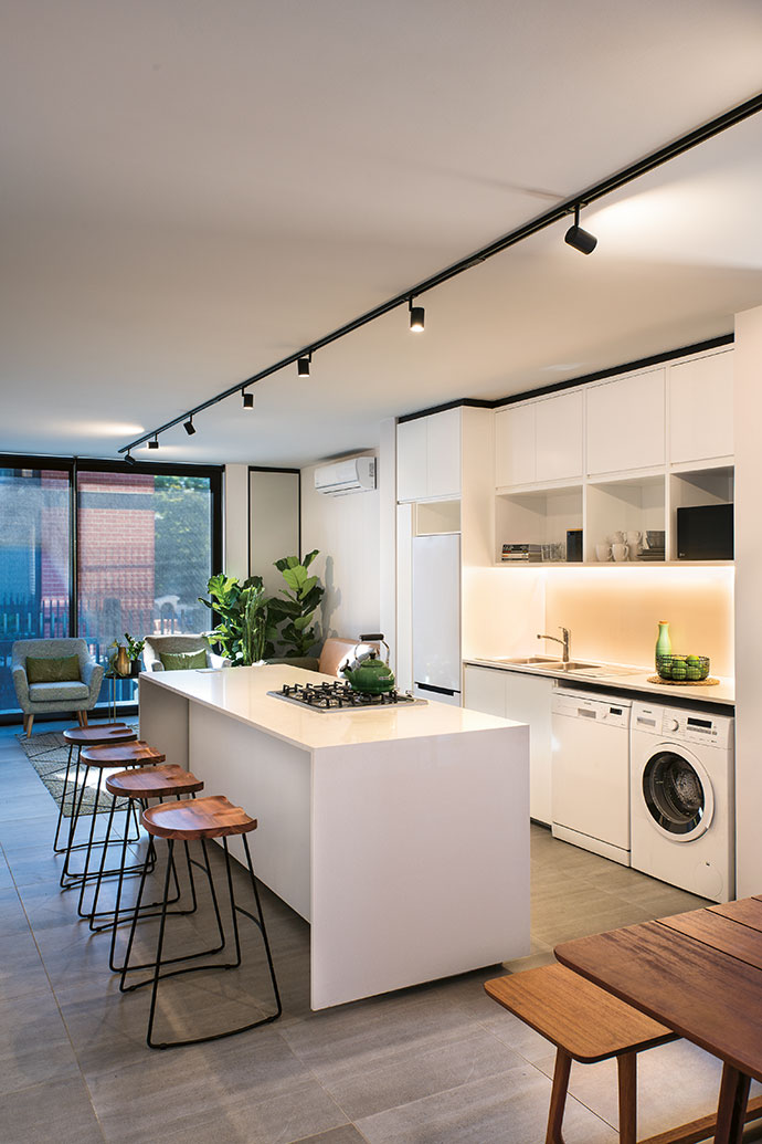 A three-bedroom unit with the kitchen in the centre of the lounge and dining area. The bar stools are from Incanda and the black track lights from Spazio.