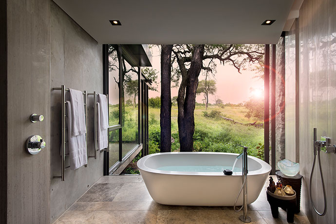 "Taking the ""bath with a view"" concept to a new level, this bathroom in one of the Karula House guest suites opens up to welcome the outside in."