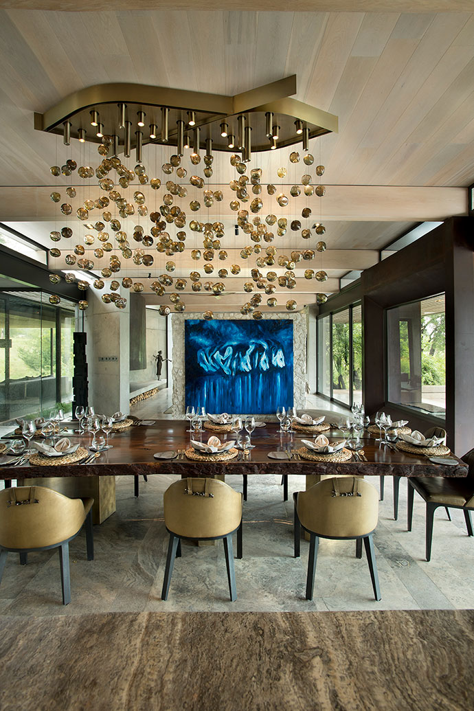 At Mapogo House, Conor Mccreedy's Blue Mapogo Brothers is a moody contrast to the playful golden bubbles of the Martin Doller chandelier above the solid Pierre Cronje leadwood dining table.