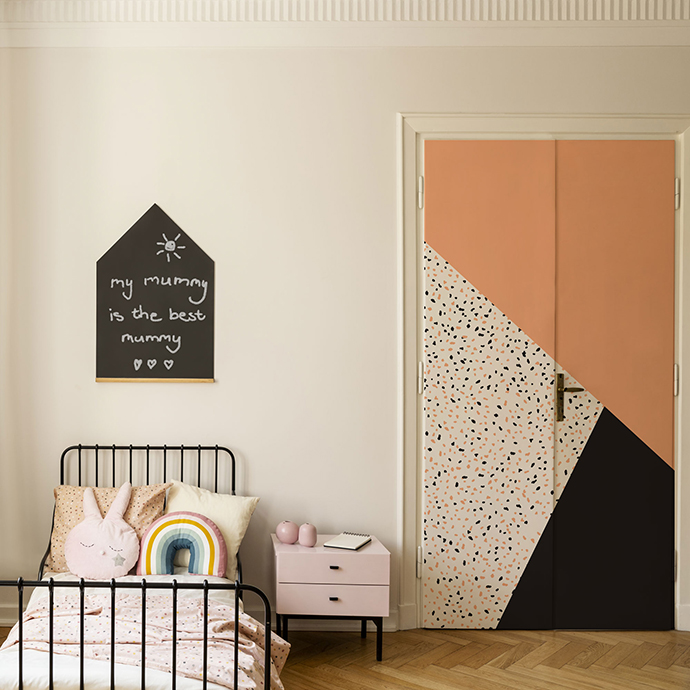 Door and cabinet next to bed with colorful cushions in kid's bed