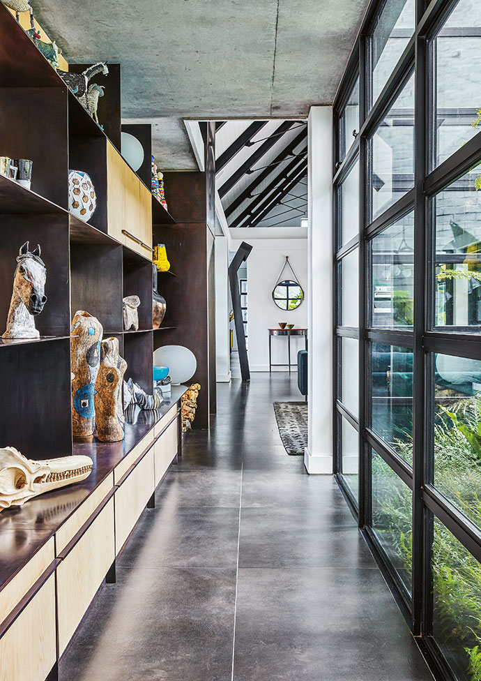 The passageway leading from the living area to the master bedroom is awash with natural light from all angles. Its glass front offers verdant garden views.