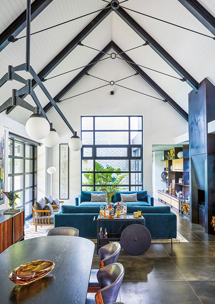 The pitched roof of the living area adds to a sense of abundant space. The large windows invite natural light to amplify the jewel tones that pop here and there.