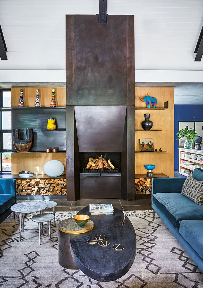 A bold fireplace by Julian McGowan finds its balance in the sofas' soft velvet textures. Ceramic pieces add pops of colour to the living room.